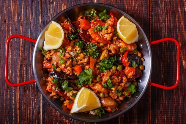 Paella z kurczakiem, chorizo, owocami morza, warzywami i szafranem podawane na tradycyjnej patelni.