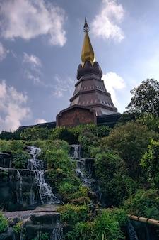 Pagoda ze złotym szczytem i wodospadami z dużą ilością roślinności dookoła w tajlandii