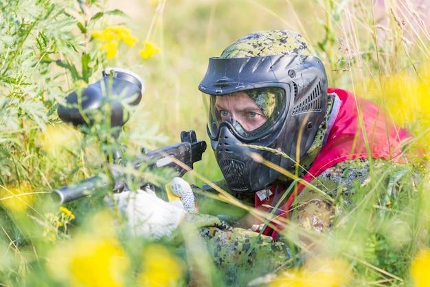 Paintball sportowy gracz w ochronnym mundurze i masce bawić się z pistoletem outdoors i skrada się w trawie.