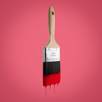 Paintbrush ładował z czerwonym kolorem kapiącym z szczecina - odizolowywającego na czerwonym tle.