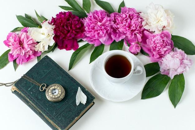 Pąki piwonii, filiżanka herbaty, stary zegarek kieszonkowy i książka