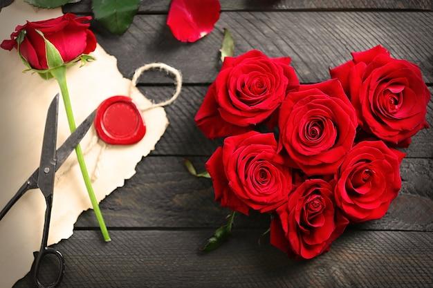Pąki świeżych czerwonych róż w kształcie serca z pustą kartą obecną na drewnianym stole