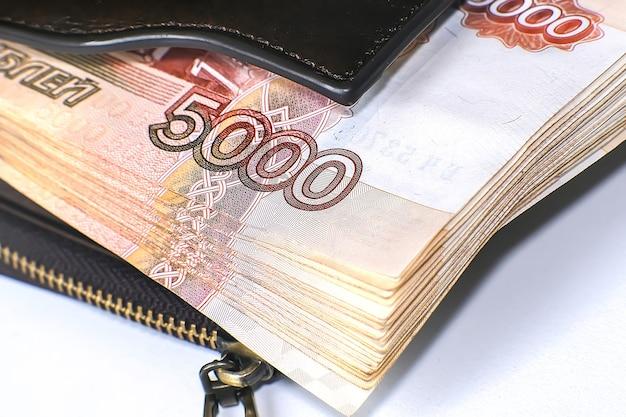 Pakiet banknotów w skórzanym portfelu. obok znajduje się stos banknotów stu dolarowych