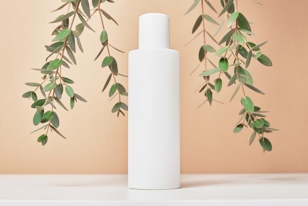 Pakiet produktów beaty. butelka kosmetyczna na pastelowym beżowym tle z liśćmi roślin. kosmetyki makieta