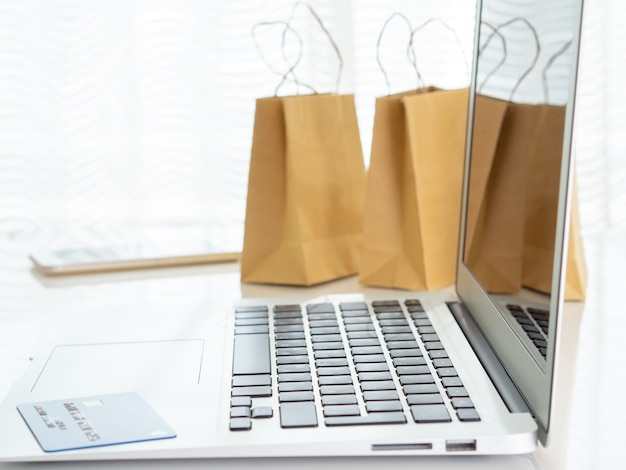 Pakiety rzemieślnicze z zakupami, smartphone na laptopa, karta kredytowa na stole przed oknem