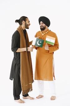 Pakistański mężczyzna i indyjscy mężczyźni w tradycyjnych strojach. przyjaciele rozmawiają na białym tle, na białym tle. umowa między krajami.