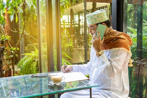 Pakistański muzułmański biznesmen używa inteligentnego telefonu komórkowego i pisze na notatniku