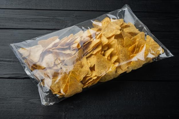 Pakowane i przyprawione nachos i opakowanie przekąsek na czarnym drewnianym stole