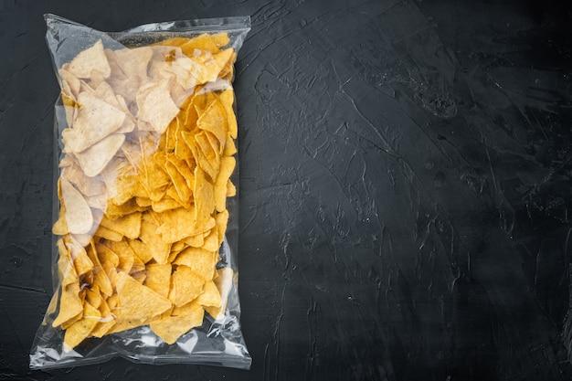 Pakowane i przyprawione nachos oraz paczka z przekąskami, na czarnym stole, widok z góry lub płasko