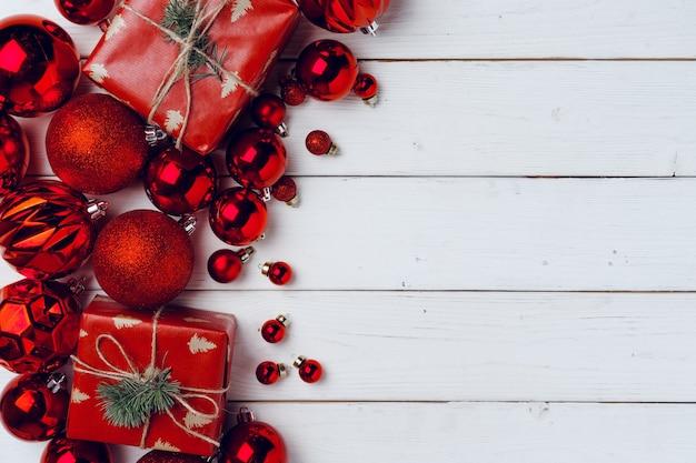 Pakowane małe prezenty świąteczne i czerwone bombki na białej drewnianej desce, widok z góry