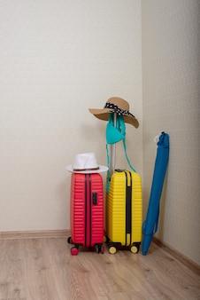 Pakowane rzeczy plażowe w dwóch walizkach, parasol plażowy i czapki w rogu pokoju