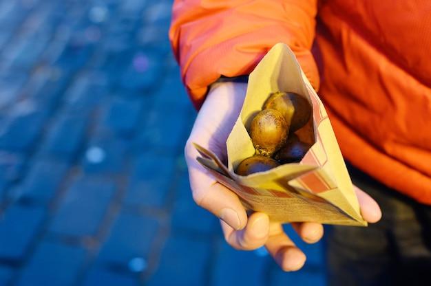 Pakowanie jadalnych pieczonych kasztanów czerwonych w rękach człowieka na ulicy.
