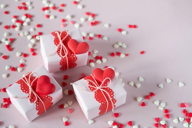 Pakowanie prezentów na walentynki. ręcznie robione pudełka i ozdoby. na różowym tle z posypką. widok z góry.