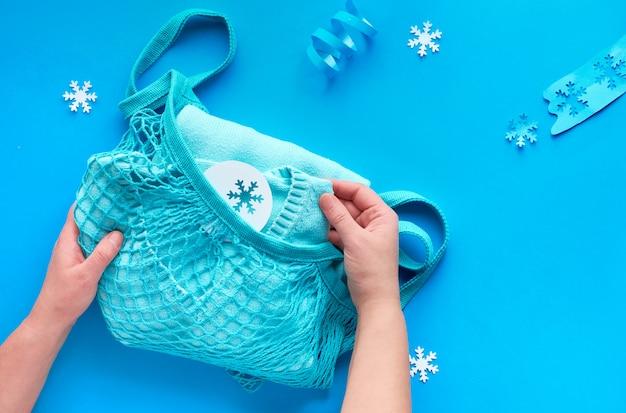 Pakowanie prezentów, niebieski sweter w sznurku lub siatkowa torba. zimowa kompozycja, mieszkanie leżało na niebieskim papierze