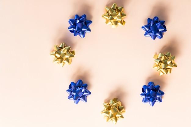 Pakowanie prezentów. prezenty. obiekt do pakowania prezentów w pudełka. okrąg złotych i niebieskich kokardek na pastelowym tle. świąteczne kokardki na prezenty dekoracyjne.