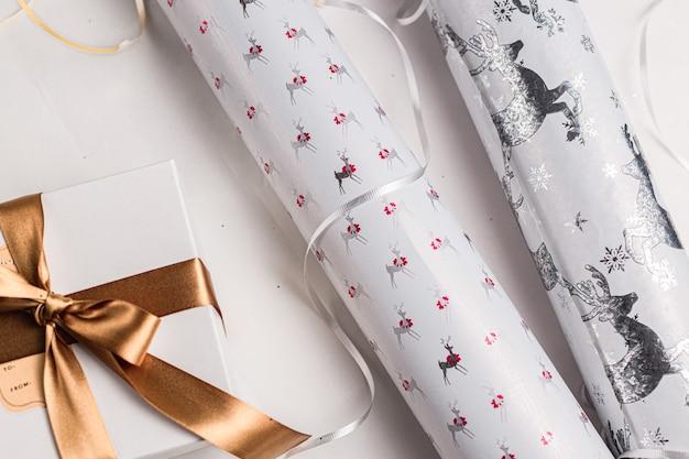 Pakowanie prezentów. świąteczny papier do pakowania na boże narodzenie,. świąteczne kolory biały, złoty, srebrny. sezon wakacyjny. ręcznie robione opakowanie na prezent.