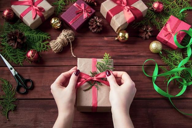 Pakowanie prezentów świątecznych. kobieta zawiązuje łuk na pudełku.