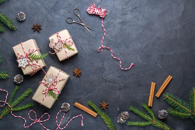 Pakowanie prezentów świątecznych. pudełka na prezenty świąteczne i dekoracje, gałązki sosny na ciemnym stole. leżał na płasko