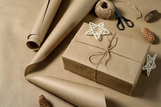 Pakowanie prezentów w brązowy papier pakowy. pudełko z papierem rzemieślniczym, nożyczkami, szyszkami i motkiem sznurka.