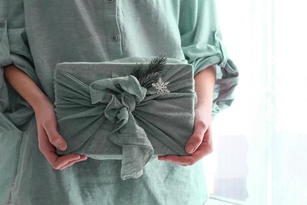 Pakowanie prezentów w tkaniny na boże narodzenie w stylu furoshiki. koncepcja przyjazna dla środowiska.
