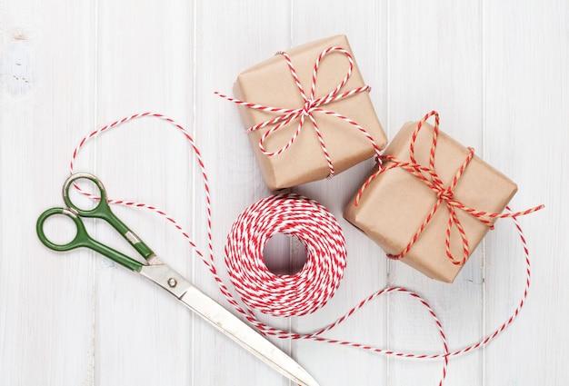 Pakowanie prezentów z pudełkami i nożyczkami na białym drewnianym stole