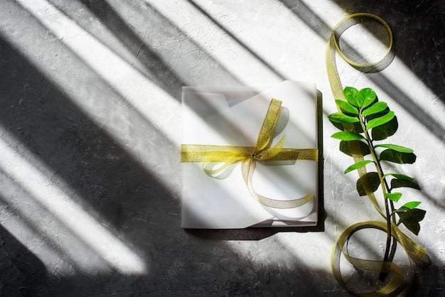 Pakowanie prezentu, w piękny biały papier, złotą wstążkę.