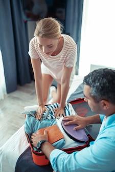 Pakowanie się. uśmiechnięta kobieta siedząca na łóżku z mężem starająca się zmieścić wszystkie swoje ubrania w małej walizce podróżnej.