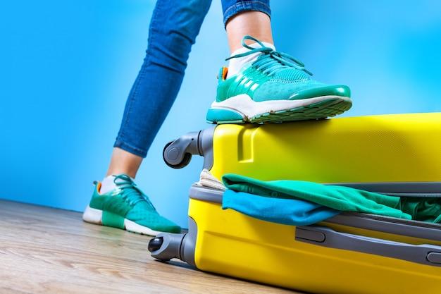 Pakowanie ubrań w żółtą walizkę. zapakuj niezbędne przedmioty do podróży lub podróży służbowej. wakacje, wakacje. koncepcja podróży