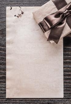 Pakowany papier prezentowy w wersji pionowej na drewnianej desce
