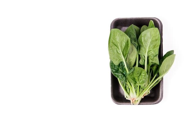 Pakowany świeży zielony szpinak. pojedynczo na białym tle. żywność ekologiczna, zdrowy styl życia