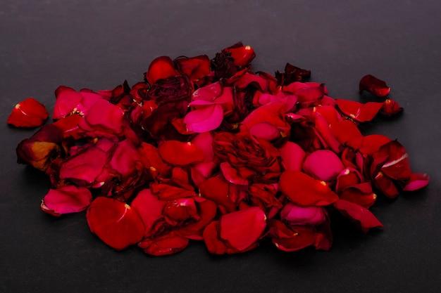 Pala jasnoczerwonych płatków róż na czarnej powierzchni
