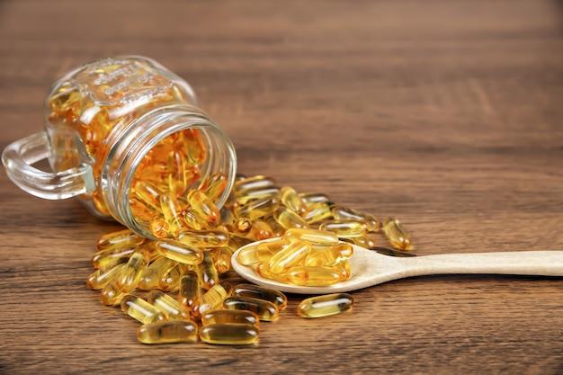 Pala kapsułki oleju z wątroby dorsza w drewnianą łyżką.