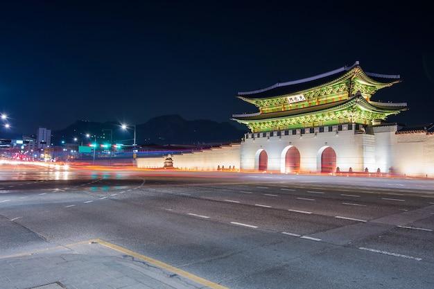 Pałac geyongbokgung i światła samochodowe nocą w seulu w korei południowej.