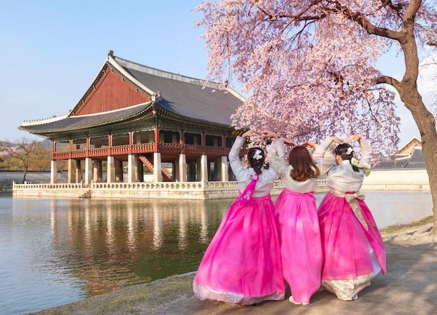 Pałac gyeongbokgung z koreańskim strojem narodowym i wiśniowym kwiatem na wiosnę, seul, korea południowa.