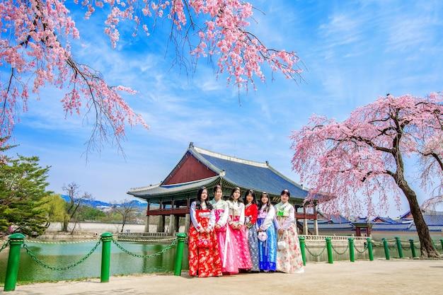 Pałac gyeongbokgung z kwitnącą wiosną wiśni i turyści w sukience hanbok