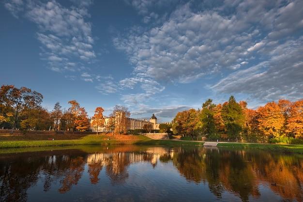 Pałac i park w gatczynie w obwodzie leningradzkim odbijają się w wodzie podczas złotej jesieni.
