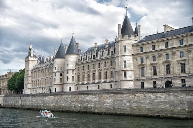 Pałac na kamiennym nasypie. wycieczka łodzią. palais de la cite w paryżu we francji. budynek pałacowy z wieżami i iglicami. zabytek architektury i designu gotyckiego. wakacje i żądza wędrówek w stolicy francji.