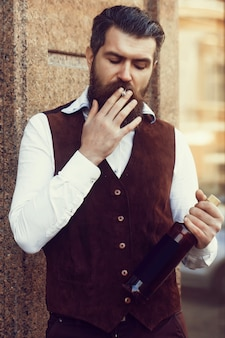 Palacz z butelką wina palący papieros