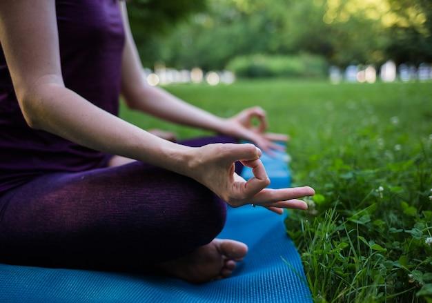 Palce dziewczyny medytującej na macie do jogi w parku