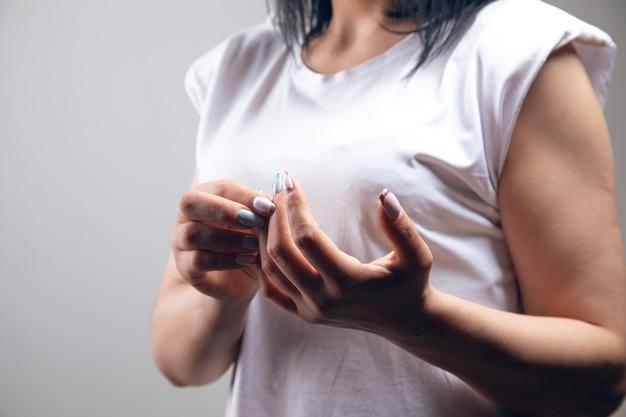 Palce kobiety bolą. ból stawów na szarej ścianie