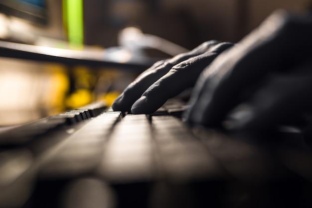 Palce naciskają na klawiaturze komputera w ciemności.