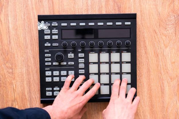 Palce producenta dźwięku odtwarzają muzykę perkusyjną na padach automatu perkusyjnego