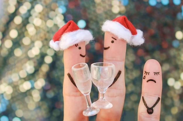 Palce sztuki szczęśliwej pary śmiejącej się w kapeluszach noworocznych. dziecko jest wściekłe i urażone. sztuka pary palców obchodzi boże narodzenie.