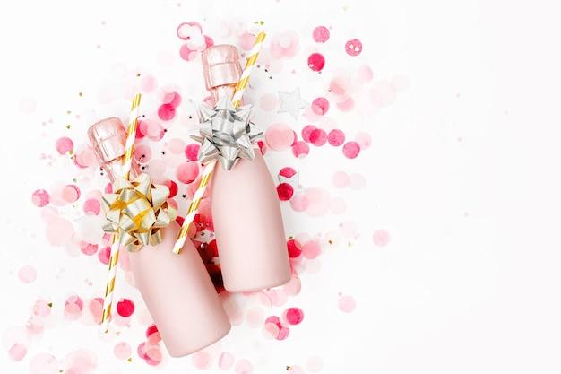 Pale pink mini butelki szampana z konfetti i blichtrem. leżał płasko. nowy rok/boże narodzenie lub wesele koncepcja tematu. płaski układanie, widok z góry