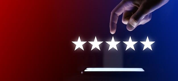 Palec człowieka klika ikonę pięciu gwiazdek. wskazuje pięciogwiazdkowy symbol, aby zwiększyć ocenę firmy. przejrzyj, zwiększ ocenę lub ranking, koncepcję oceny i klasyfikacji.