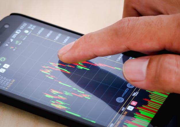 Palec mężczyzny dotyka ekranu telefonu, który przegląda informacje giełdowe