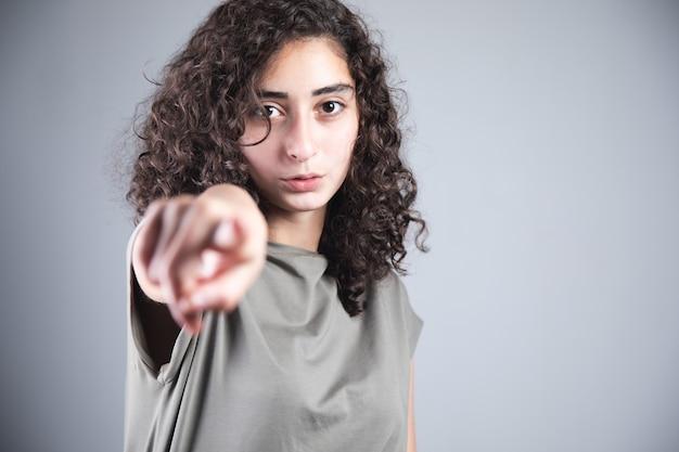 Palec młodej kobiety, który podpisujesz na szarym tle
