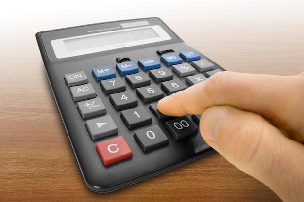 Palec naciska klawisz elektronicznego kalkulatora