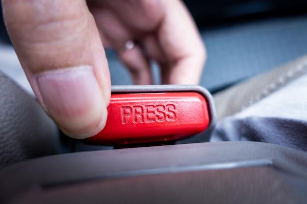 Palec naciskając i zwalniając klamrę pasa w samochodzie
