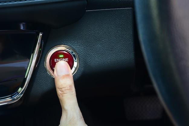Palec naciskając okrągły czerwony przycisk włączania i wyłączania silnika na desce rozdzielczej w luksusowym samochodzie